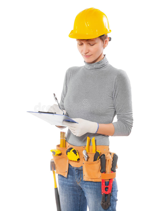 Feamale worker with construction tools holding clipboard writing royalty free stock photography