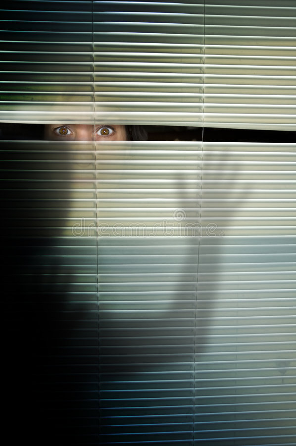 Fear. A womans wide open brown eyes stare in fear from between the slats of blinds and the shadow cast of someone outside
