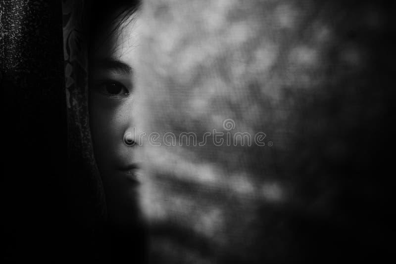 Fear girl hiding behind curtain with shadow edge royalty free stock photos