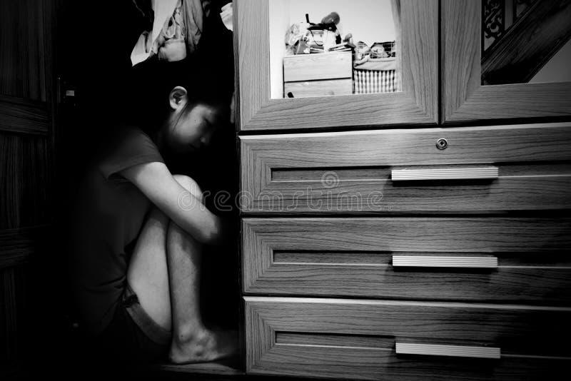 Fear girl hiding in closet stock photography