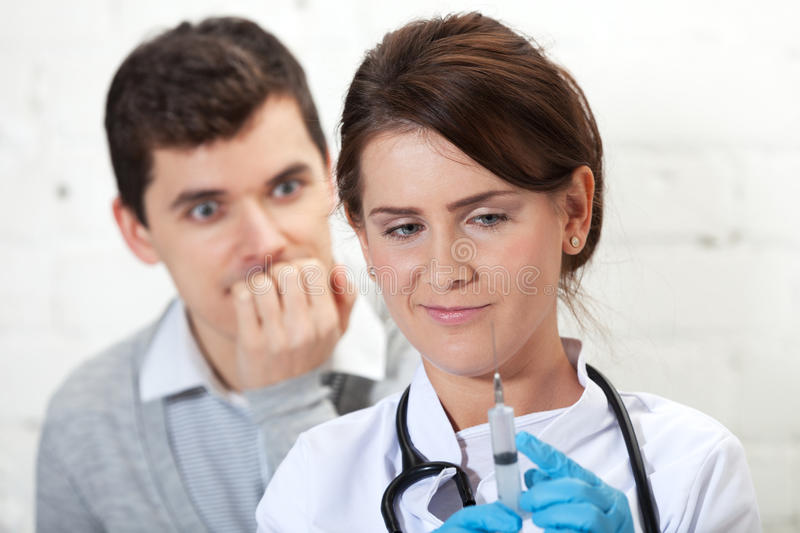 Fear of injection. Patient is afraid of injection nurse is about to make stock image