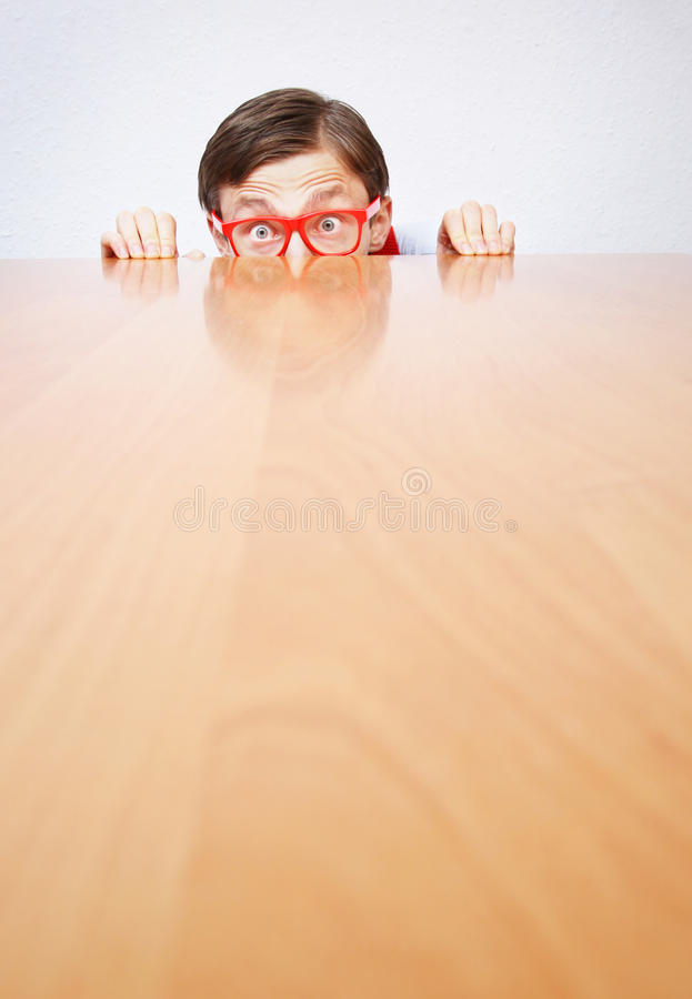 Fear in the office. Funny nerd hiding behind a desk royalty free stock photos