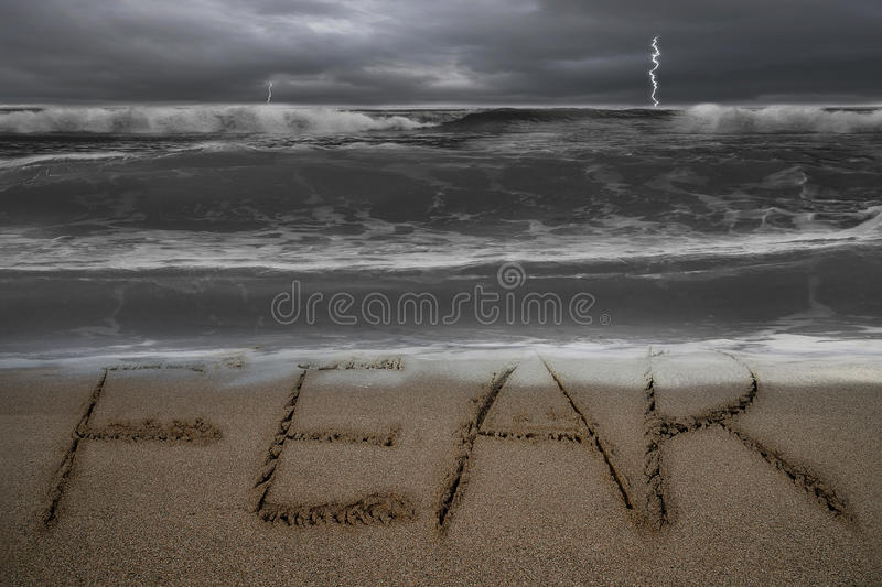 Fear word hand written on sand beach with stormy ocean. Fear word hand written on sand beach with dark stormy ocean background royalty free stock photography