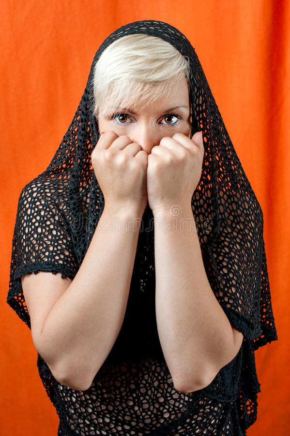 Feared girl covering her face. Blond girl with black veil hold her fists over face being scared stock photos