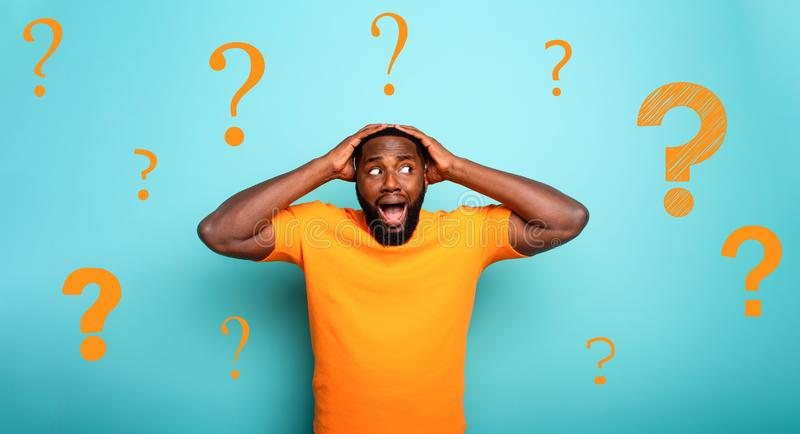 Feared and shocked expression of a boy with many questions . cyan colored background stock photography
