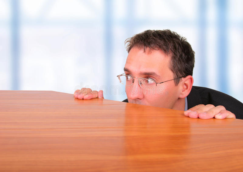 Fearful business man. Hide behind table royalty free stock photos