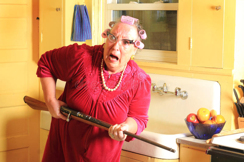 Fearful Granny with Rifle. A fearful senior gray haired granny lady wearing cat eye glasses, pearls and curlers in her hair in an old fashioned yellow kitchen royalty free stock images