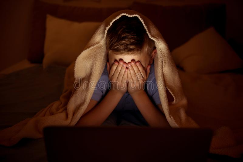 Terrified little boy spending evening at home stock photography
