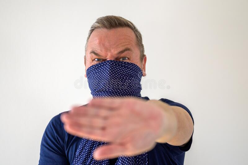 Fearful man social distancing during pandemic. Fearful man wearing a facial guard over his nose and mouth enforcing social distancing during the Covid-19 or royalty free stock photography