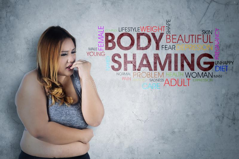 Fearfully obese woman with text of body shaming stock images