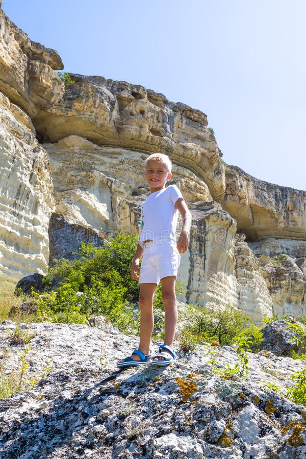 fearless adorable little happy boy stand on steep edge of limestone plateau overlooking the valley stock photo