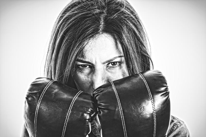 Fearless and furious modern business woman with boxing gloves is. Closeup portrait of a determined female boxer. Confident, fearless and furious modern business royalty free stock image