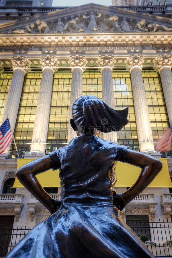 The Fearless Girl statue facing The New York Stock Exchange NYSE building stock photos