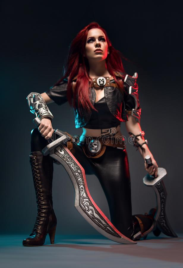 Fearless redhead warrior woman in leather costume with swords. Posing on dark background stock photo