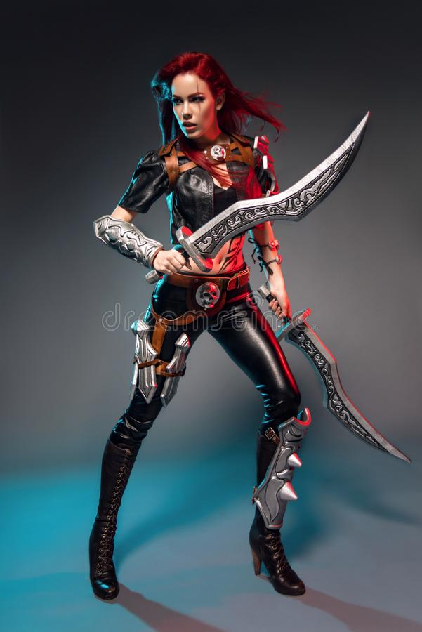 Fearless redhead warrior woman in leather costume with swords. Posing on dark background stock image