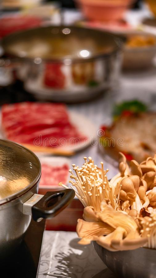 Feast!. Close-up of oyster, enoki and shiitake mushrooms next to pot of soup with blurry background of table full of food stock photography