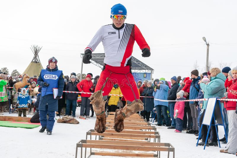 Feast of reindeer herders and fishermans. Jumping through the sleds royalty free stock photo