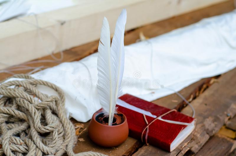 Feather quill pen and old leather bound note book stock images
