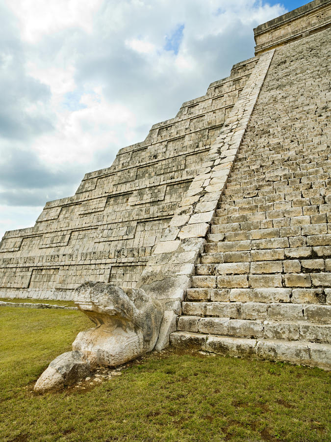 Feathered serpent in pyramid Kukulkan Chichen Itza. Feathered serpent at the foot of pyramid Kukulkan in Chichen Itza royalty free stock photos