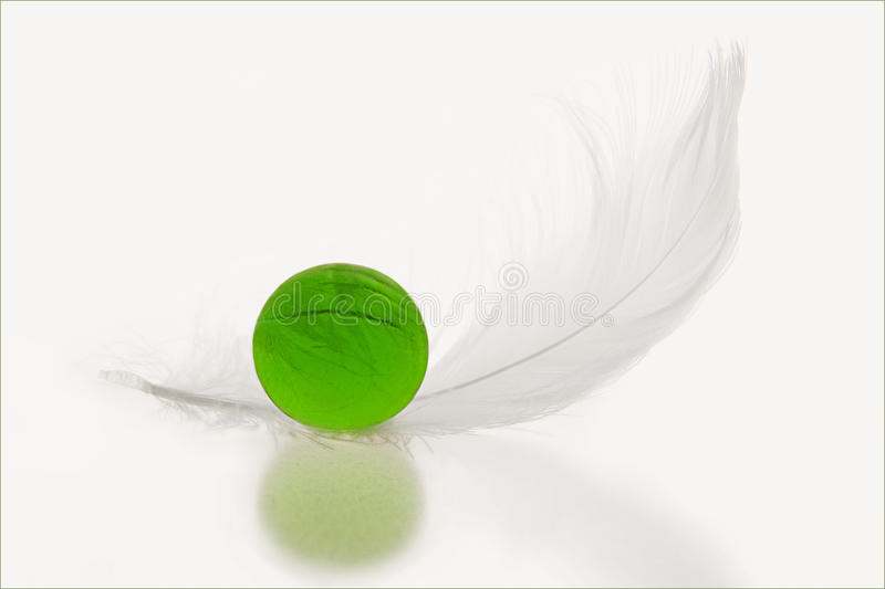 Featherweight. Glass marble with a white gull feather on a plain background royalty free stock image