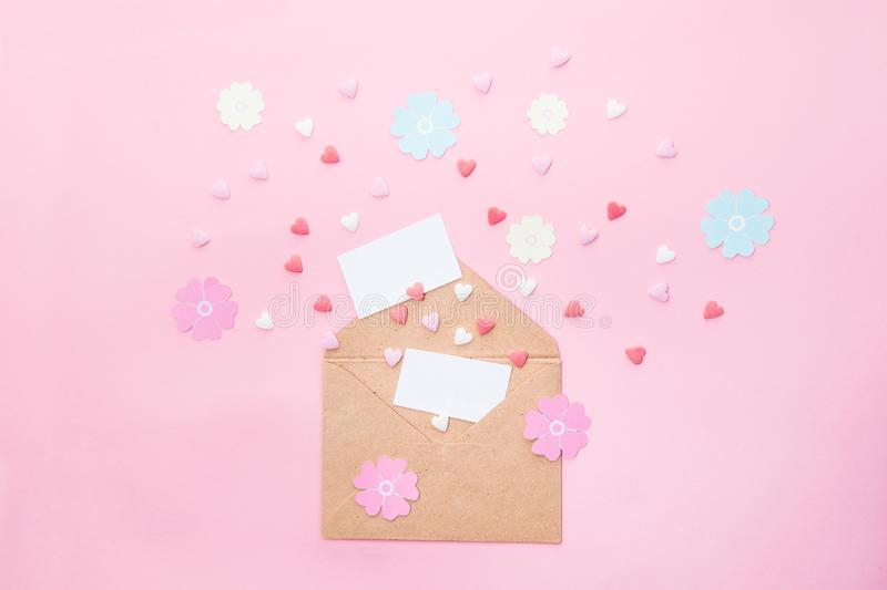 Feative composition of empty cards, multicolor sweets sugar candy hearts, handmade paper flowers fly out of craft paper envelope o royalty free stock image