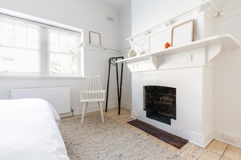 Feature fireplace in a luxury renovated Danish styled bedroom. Feature open fireplace in a luxury renovated Danish styled bedroom stock photo
