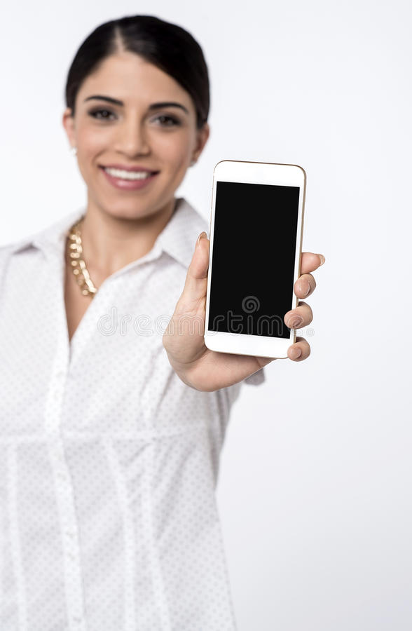 Featured cell phone on sale now !. Pretty female representative showing new mobile phone royalty free stock images