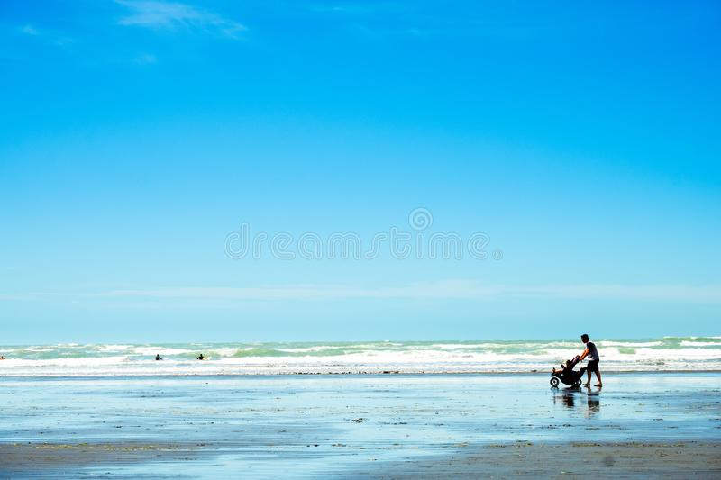 \'2018, FEB 4 - Christchurch, New Zealand, A Father took twin baby in baby trolley walking at the beautiful beach on a sunny blue. Sky day royalty free stock photo