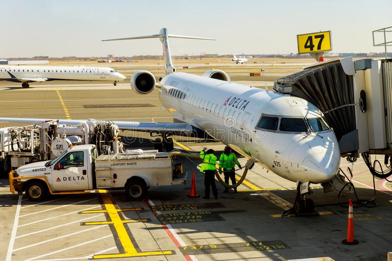Small jet airplane with attached at airport gate terminal during DELTA JFK International Airport. FEB 14, 2019 JFK NEW YORK, USA: Small jet airplane with royalty free stock photography