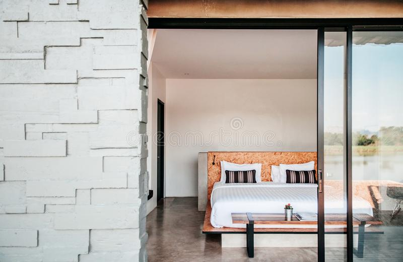 White contemporary hotel style bedroom with gray color stone wall exterior decoration royalty free stock photography