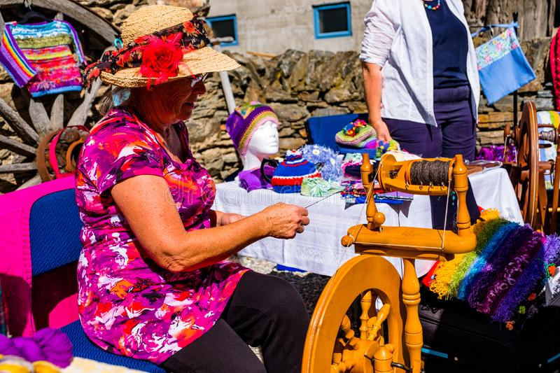 2019 FEB 12, New Zealand, Cromwell, A lady using the old traditional wooden yarn machine in market. L stock photos