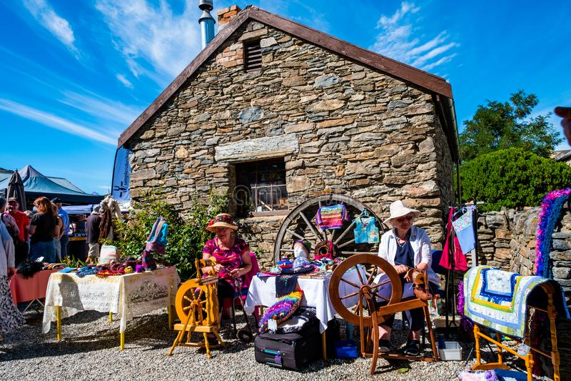 2019 FEB 12, New Zealand, Cromwell, A lady using the old traditional wooden yarn machine in market. L stock images