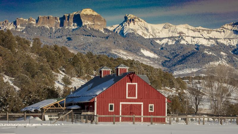 FEB 24, 2019, RIDGWAY, COLORADO USA - Red barn under Cimeron Mountains outside of Ridgway Colorado on State Route 550 royalty free stock image