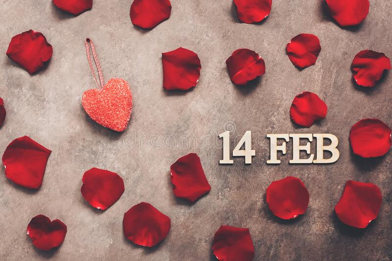 FEB 14, Valentine`s Day. Red rose petals and heart on adark brown rustic background. Top view, flat lay,toned.  royalty free stock photography
