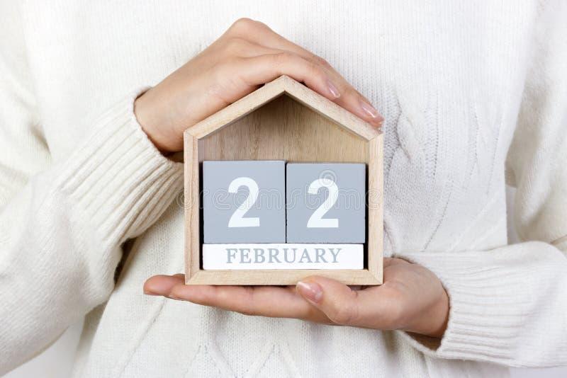 22 febbraio nel calendario la ragazza sta tenendo un calendario di legno Giorno di George Washington, giorno internazionale di su immagini stock