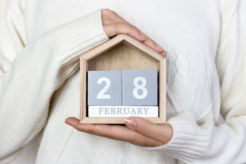 28 febbraio nel calendario la ragazza sta tenendo un calendario di legno Giorno raro di malattia, martedì grasso, giorno di panca fotografia stock