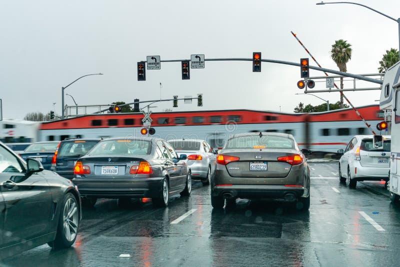 2 febbraio 2019 Sunnyvale/CA/U.S.A. - veicoli che aspettano ad un semaforo rosso; treno ad alta velocità che passa nei precedenti fotografia stock