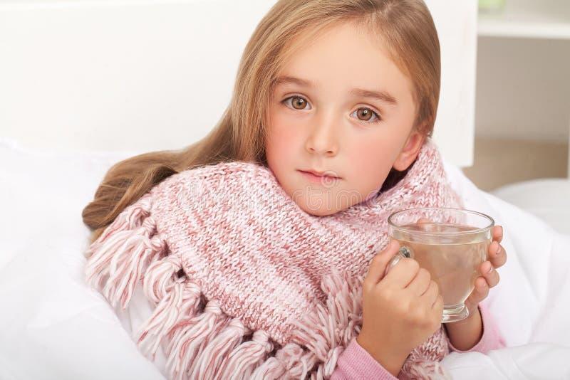 Feber, förkylning och influensa - mediciner och varmt te i nära, sjuk flicka I royaltyfri fotografi