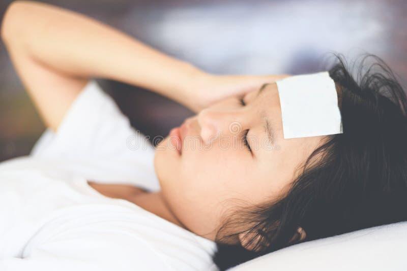 Feberbarn med att mäta den sjuka temperaturen av ungen - barn med hög feber och att lägga i sänghanden som rymmer på pannan och a royaltyfria foton