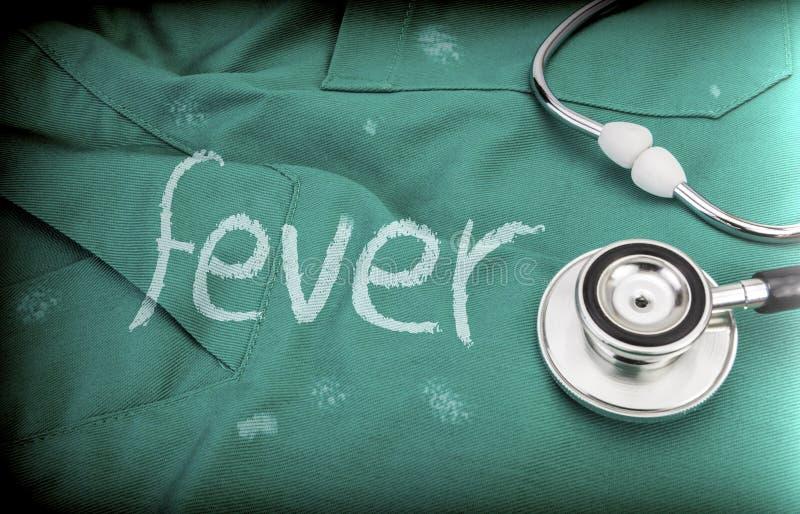 A febre da palavra pintou branco no uniforme médico ao lado de um estetoscópio fotos de stock royalty free