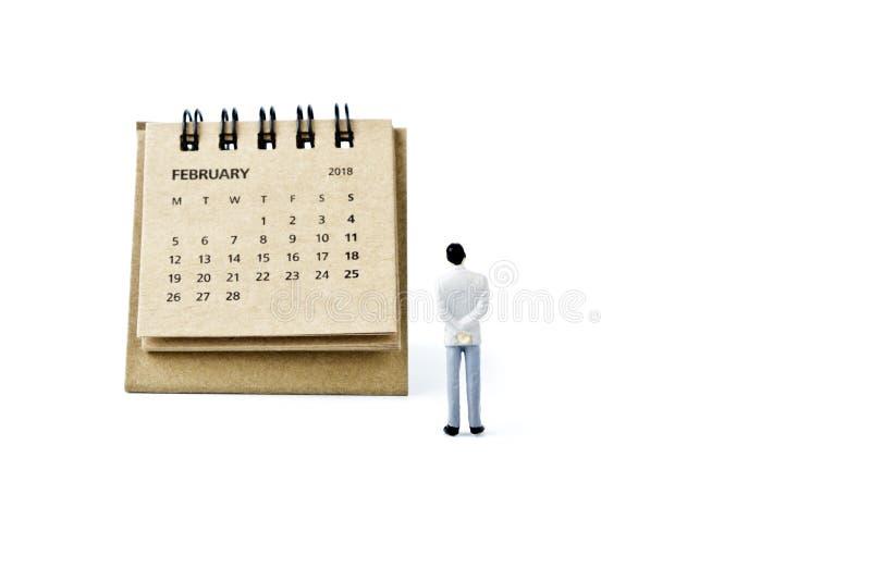 febrero Haga calendarios la hoja y al hombre plástico miniatura en la parte posterior del blanco fotos de archivo