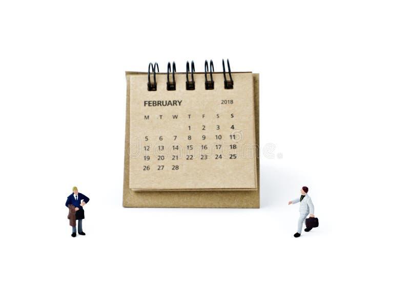 febrero Haga calendarios la hoja y a los hombres de negocios plásticos miniatura en wh fotografía de archivo