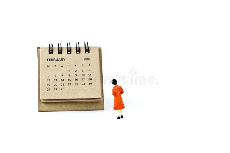 febrero Haga calendarios la hoja y a la mujer plástica miniatura en los vagos blancos foto de archivo