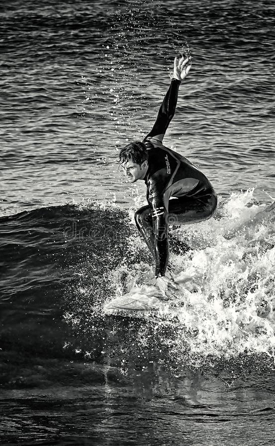 Februar 2019 Surfer, der eine Welle allein, Seespray, Wassersport, Cala-mesquida Strand, Mallorca, Spanien im Februar 2019 reitet stockbild