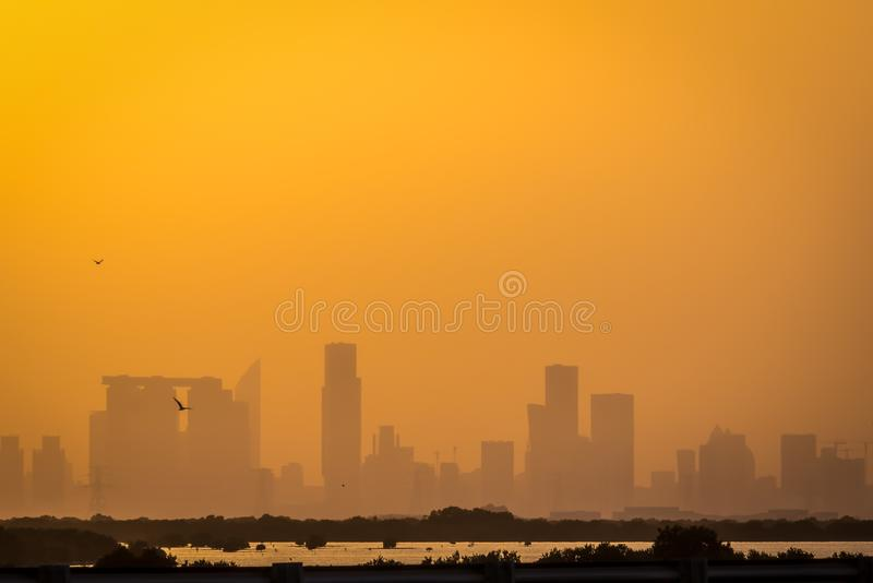 Februari 23, 2018: Abu Dhabi City Skyscrapers Covered med orange dus royaltyfri foto