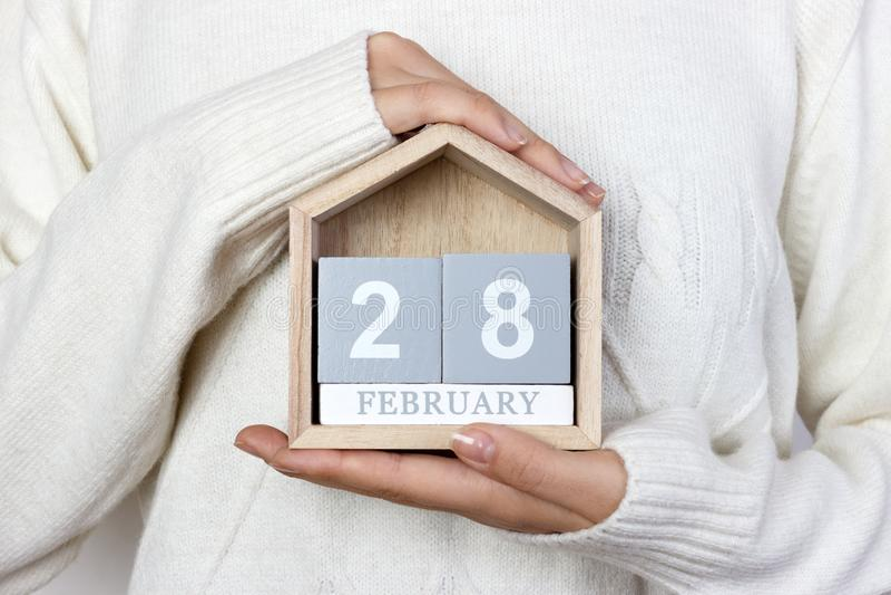 28 februari in de kalender het meisje houdt een houten kalender Zeldzame Ziektedag, Vastenavond, Internationale Pannekoekdag stock foto