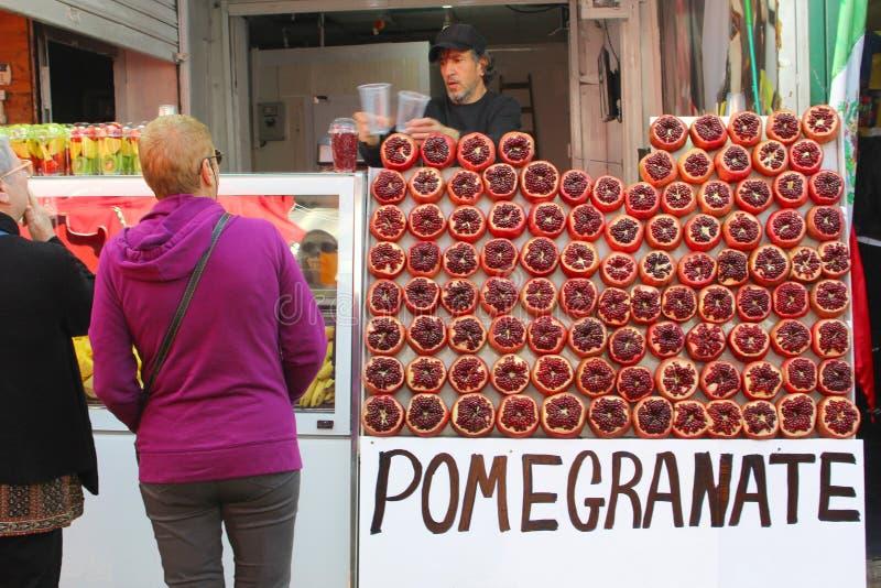 Februari 2019, kvinnor köper mannen säljer granatäpplefruktsafter, Carmel Market, Tel Aviv arkivbilder