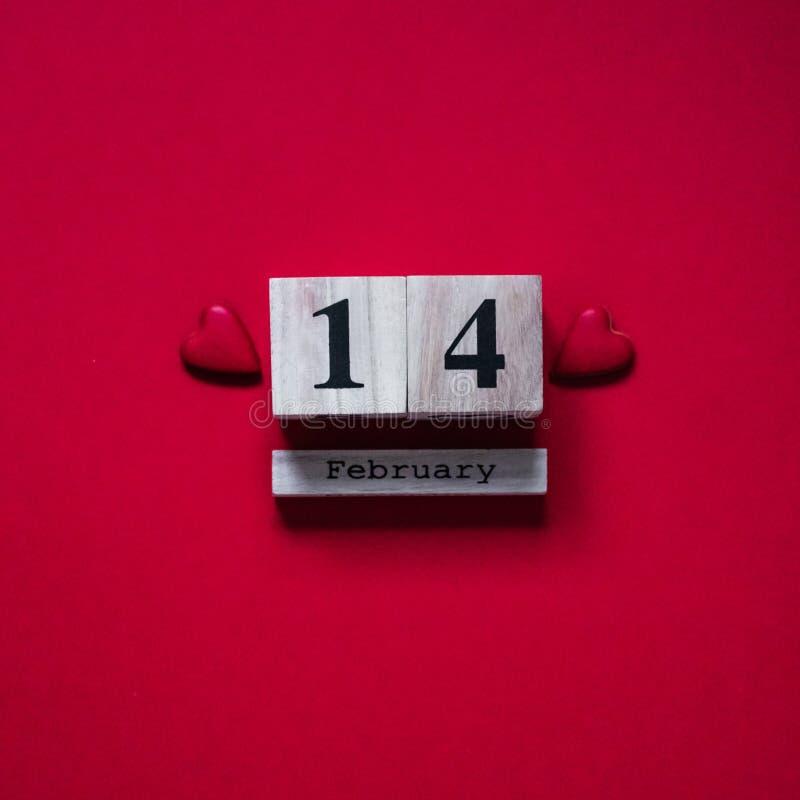 14 Februari Röd bakgrund med träkalendern Begrepp för dag för valentin` s Begrepp för valentindagkort royaltyfri fotografi