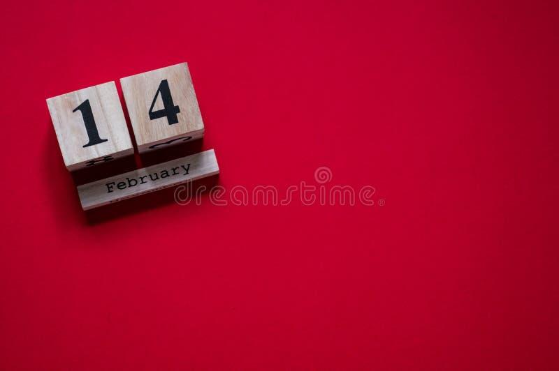 14 Februari Röd bakgrund med träkalendern Begrepp för dag för valentin` s Begrepp för valentindagkort royaltyfria foton
