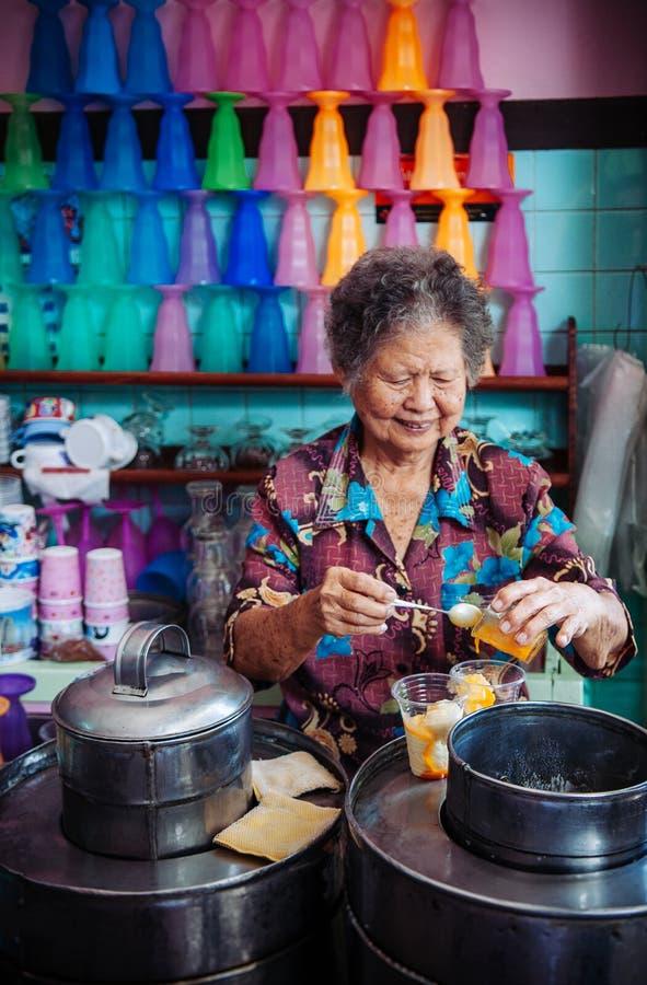 FEBRUARI 28, 2013 Songkhla, TAHILAND - asiatisk kvinna som gör kokosnöten att mjölka glass med krämig äggula, traditionellt sött  arkivbilder
